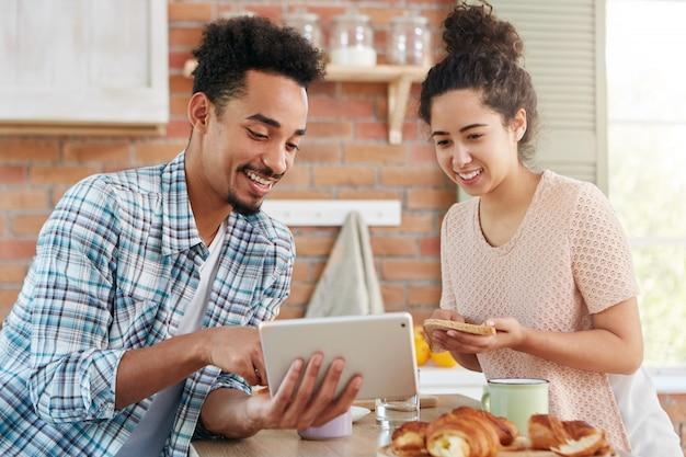 Bebaarde jongeman draagt geruit overhemd toont iets op tabletcomputer aan zijn vrouw die broodjes maakt