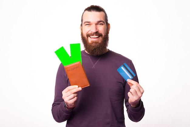 Bebaarde jongeman houdt een paspoort vast met een paar kaartjes erin en een creditcard
