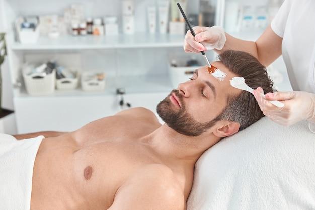 Bebaarde jongeman is ontspannen terwijl schoonheidsspecialist witte klei op zijn gezicht met borstel bij de schoonheidssalon verspreidt.
