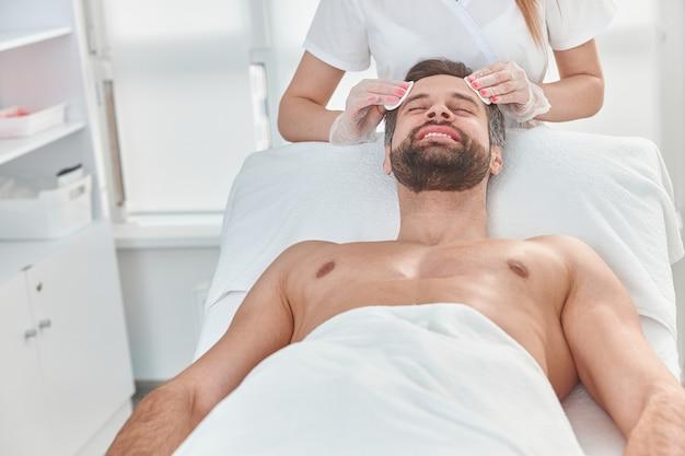 Bebaarde jongeman krijgt schoonheidsbehandeling, huidverzorging. aantrekkelijk mannetje krijgt gezichtsverzorging door schoonheidsspecialiste bij kuuroordsalon.