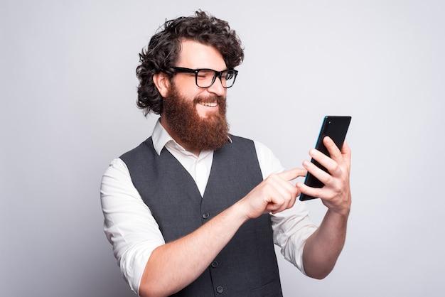 Bebaarde jongeman met bril lacht en typt in een tablet