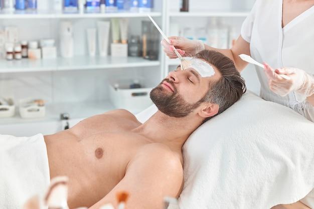 Bebaarde jongeman ontspant terwijl schoonheidsspecialist witte klei op zijn gezicht verspreidt