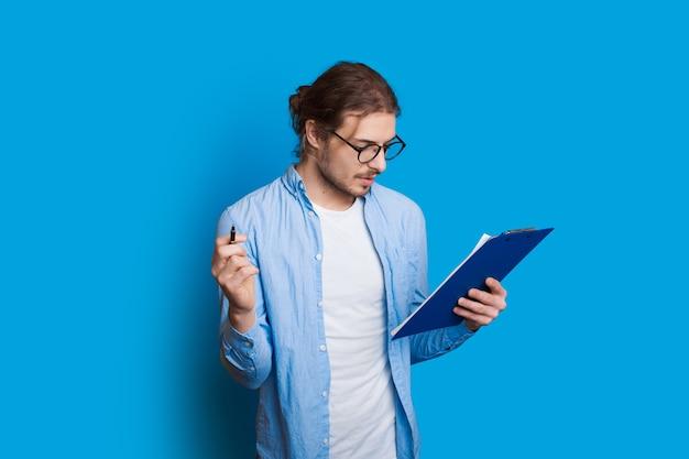 Bebaarde jongen met lang haar kijkt in een notitieboekje door een bril en poseren op een blauwe muur