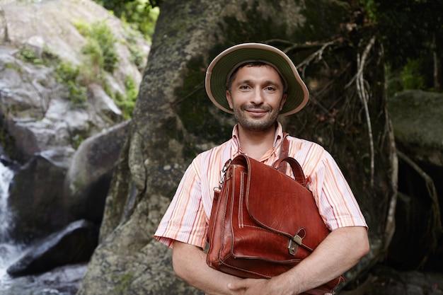 Bebaarde kaukasische botanicus of bioloog van middelbare leeftijd die panamahoed draagt, aktetas met beide handen vasthoudt met vriendelijke glimlach, genietend van zijn onderzoek bij veldwerk in het regenwoud