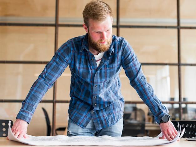 Bebaarde kaukasische mens die blauwdruk in bureau bekijkt
