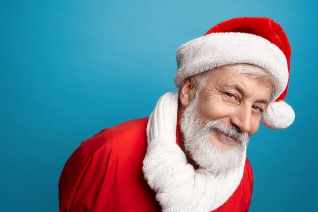 Bebaarde kerstman in rode hoed en witte sjaal in studio