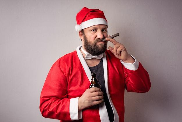 Bebaarde kerstman met een lange baard in kersttrui die bier vasthoudt en zijn sigaar rookt