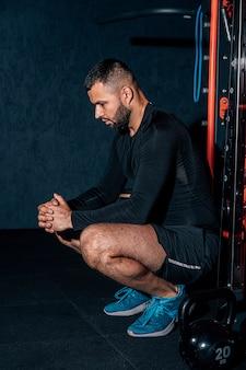 Bebaarde knappe gespierde atletische man met een handdoek in de kleedkamer na het trainen.
