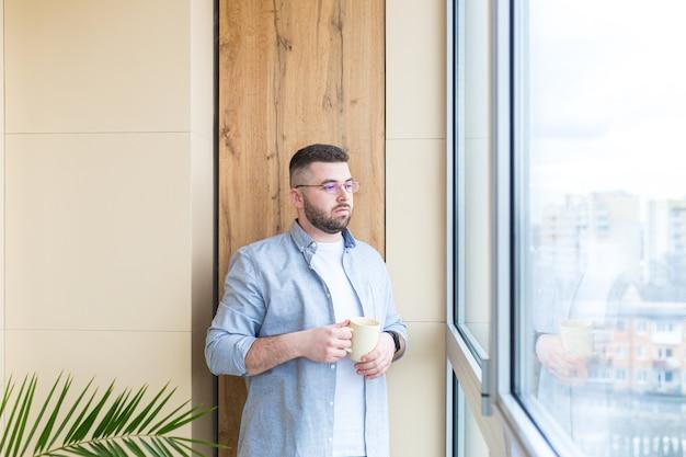 Bebaarde knappe man staat bij raam met een kopje in zijn hand op het balkon en drinkt een warme koffie of thee man in vrijetijdskleding geniet van doorkijk op kantoor of thuis ontspannen of time-out op het werk