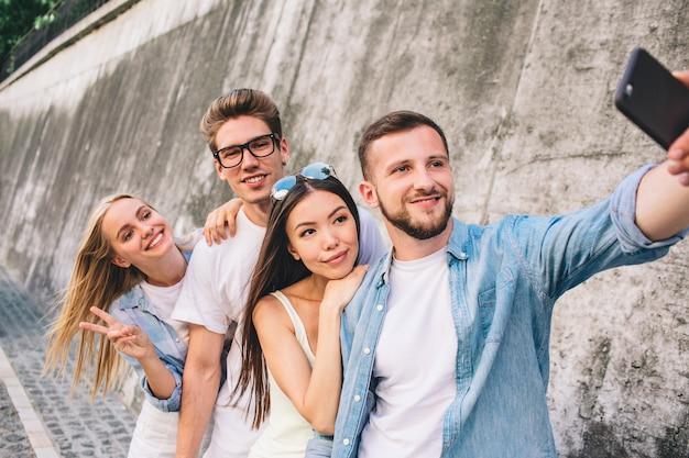 Bebaarde knappe man staat voor zijn vrienden en neemt selfie met hen