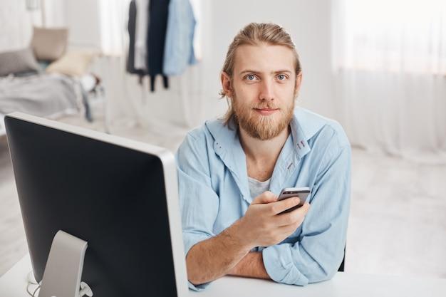 Bebaarde knappe mannelijke kantoormedewerker met zachte glimlach leest melding op smartphone, zit voor scherm op coworking-ruimte met mobiele telefoon, stuurt feedback naar collega's, bladert door internet