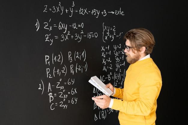 Bebaarde leraar in vrijetijdskleding die formules op schoolbord herschrijft vanuit zijn schrift voordat hij zijn online publiek een taak geeft