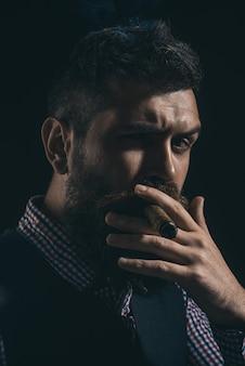 Bebaarde macho met sigaar. gentleman in geruit overhemd en vest rokende sigaar. elegante man met baard, snor rook sigaar. klassiek uitstekend mannelijk portret. bebaarde man in stijlvolle retro kleding.