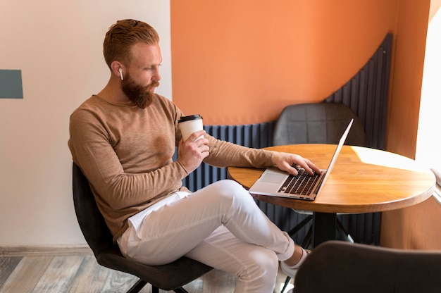 Bebaarde man aan het werk aan zijn bureau terwijl hij een kopje koffie vasthoudt