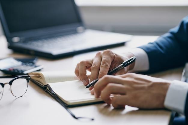 Bebaarde man aan het werk voor een laptop in de kantooremoties officieel