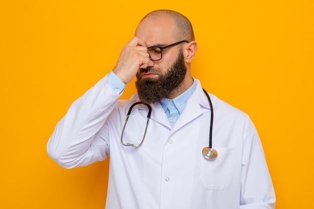 Bebaarde man arts in witte jas met stethoscoop om de nek met een bril die er geïrriteerd en uitgeput uitziet en de neus tussen gesloten ogen aanraakt