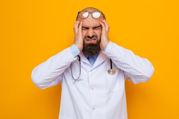 Bebaarde man arts in witte jas met stethoscoop om de nek met een bril die er geïrriteerd en uitgeput uitziet en zijn gezicht met handen aanraakt