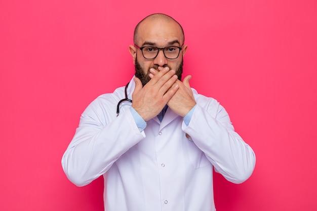 Bebaarde man arts in witte jas met stethoscoop om de nek met een bril die er geschokt uitziet en de mond bedekt met handen