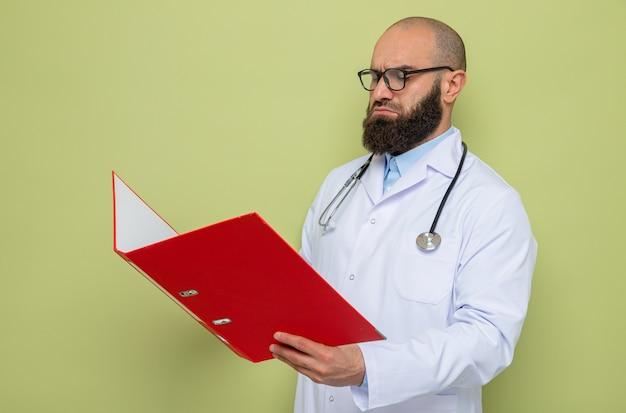 Bebaarde man arts in witte jas met stethoscoop om de nek met een bril met een kantoormap die er met een serieus gezicht naar kijkt
