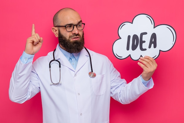 Bebaarde man arts in witte jas met stethoscoop om nek bril houden toespraak bubble bord met woord idee opzij kijken met ernstig gezicht wijsvinger tonen