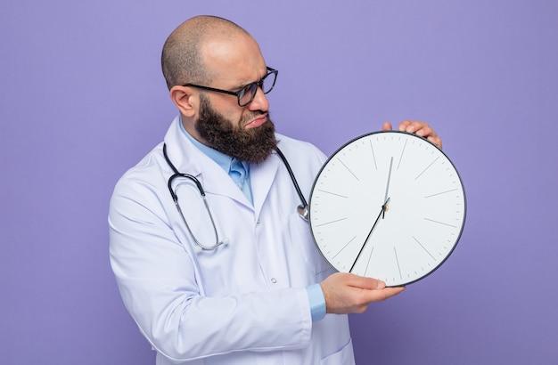 Bebaarde man arts in witte jas met stethoscoop om nek die klok vasthoudt en ernaar kijkt, geïntrigeerd met een serieus gezicht
