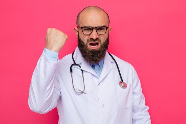 Bebaarde man arts in witte jas met stethoscoop om nek met bril die boos en opgewonden kijkt en vuist toont