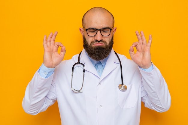 Bebaarde man arts in witte jas met stethoscoop om nek met bril die meditatiegebaar maakt met vingers die proberen te ontspannen over oranje achtergrond