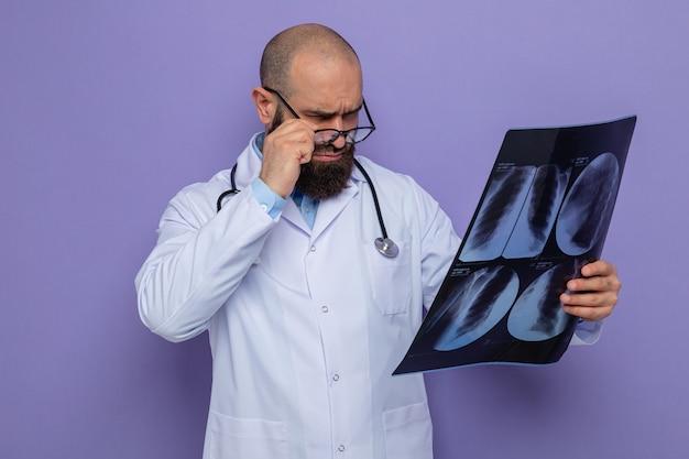 Bebaarde man arts in witte jas met stethoscoop om nek met bril die röntgenfoto's vasthoudt en er nauwlettend naar kijkt