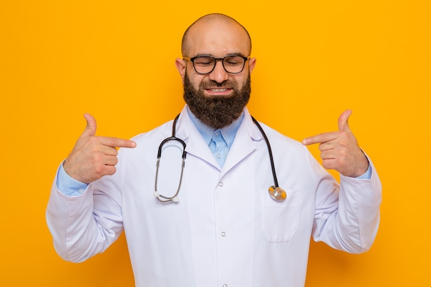 Bebaarde man arts in witte jas met stethoscoop om nek met bril glimlachend zelfverzekerd wijzend op zichzelf