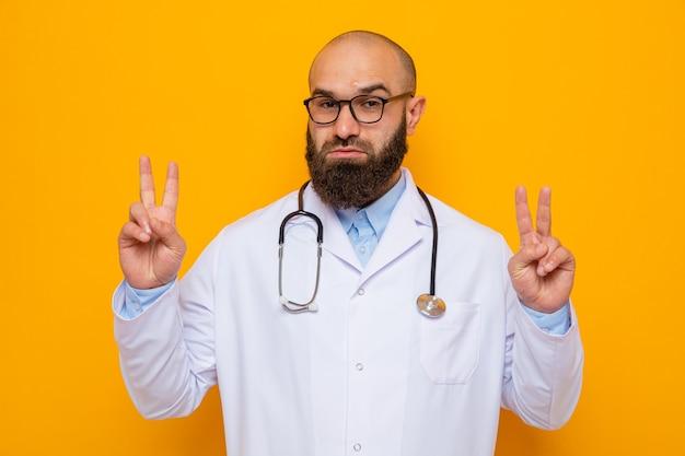 Bebaarde man arts in witte jas met stethoscoop om nek met bril kijken naar camera met zelfverzekerde uitdrukking met v-teken staande over oranje achtergrond