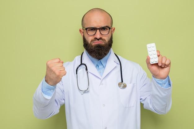 Bebaarde man arts in witte jas met stethoscoop om nek met bril met blaar met pillen op zoek met een serieus gezicht met vuist
