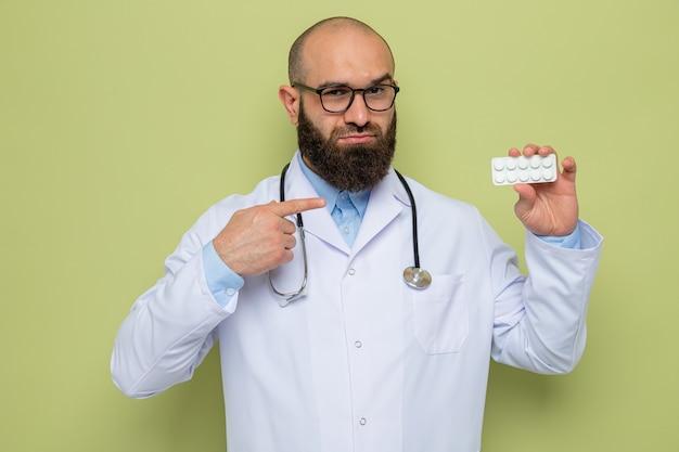 Bebaarde man arts in witte jas met stethoscoop om nek met bril met blister met pillen wijzend met wijsvinger naar het glimlachend zelfverzekerd staande over groene achtergrond