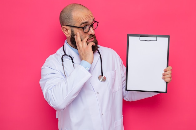 Bebaarde man arts in witte jas met stethoscoop om nek met bril met klembord met blanco pagina's die er verbaasd naar kijken