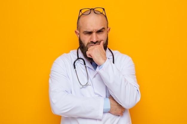 Bebaarde man arts in witte jas met stethoscoop om nek met bril op zijn hoofd kijken met fronsend gezicht met hand op zijn kin