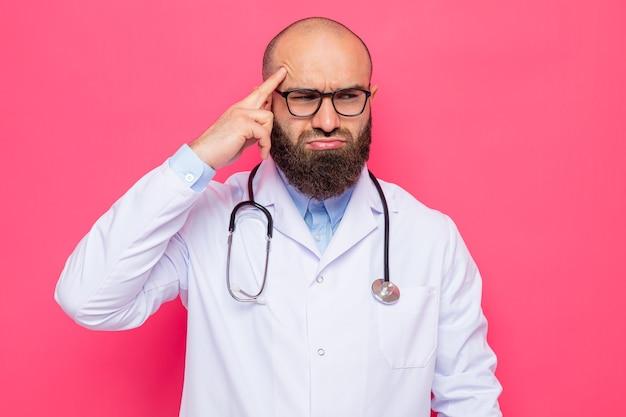 Bebaarde man arts in witte jas met stethoscoop om nek met bril opzij kijkend verward wijzend met wijsvinger naar zijn slaap