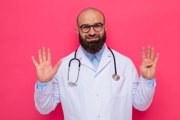 Bebaarde man arts in witte jas met stethoscoop om nek met een bril die er glimlachend uitziet en nummer negen met vingers toont