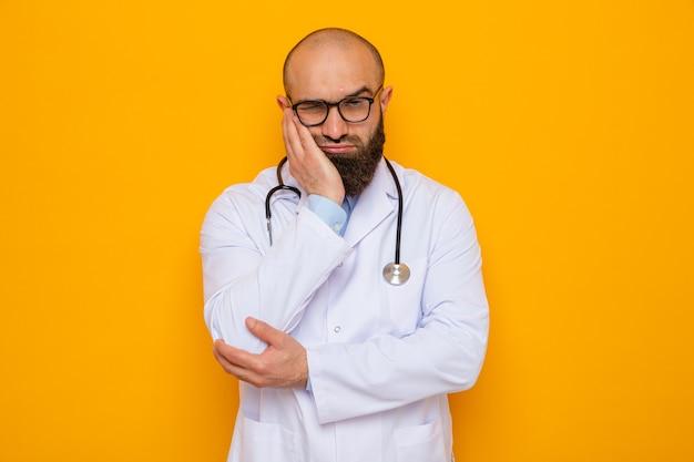 Bebaarde man arts in witte jas met stethoscoop om nek met een bril die er moe en verveeld uitziet