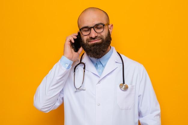 Bebaarde man arts in witte jas met stethoscoop om nek met een bril die lacht met een blij gezicht tijdens het praten op mobiele telefoon
