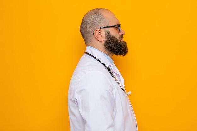 Bebaarde man arts in witte jas met stethoscoop om nek met een bril die zijwaarts staat met een serieus gezicht over oranje achtergrond