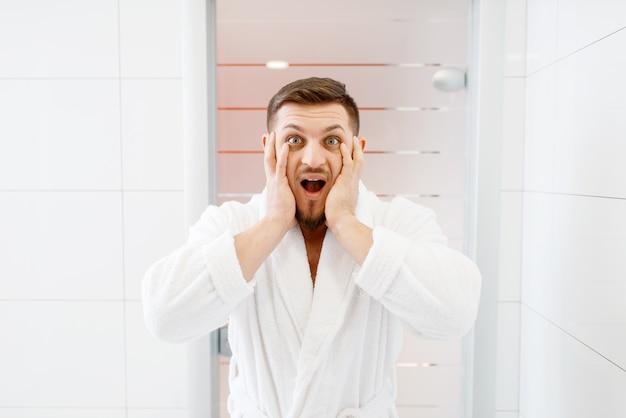 Bebaarde man bang door zijn verschijning in de spiegel in de badkamer, ochtendhygiëne.