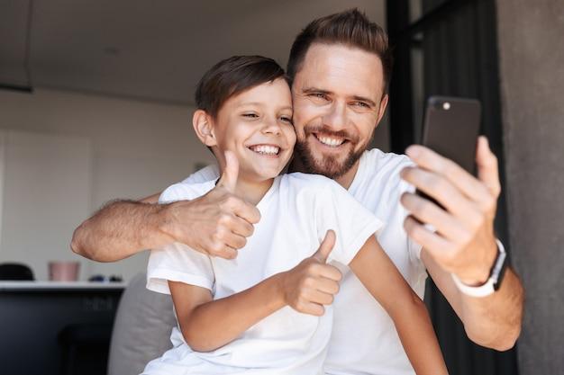 Bebaarde man binnenshuis thuis met zijn zoon een selfie maken.