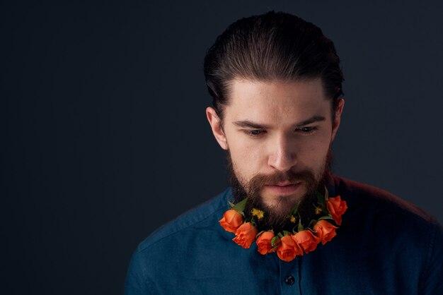 Bebaarde man bloemen in een baard close-up romantiek donkere achtergrond.
