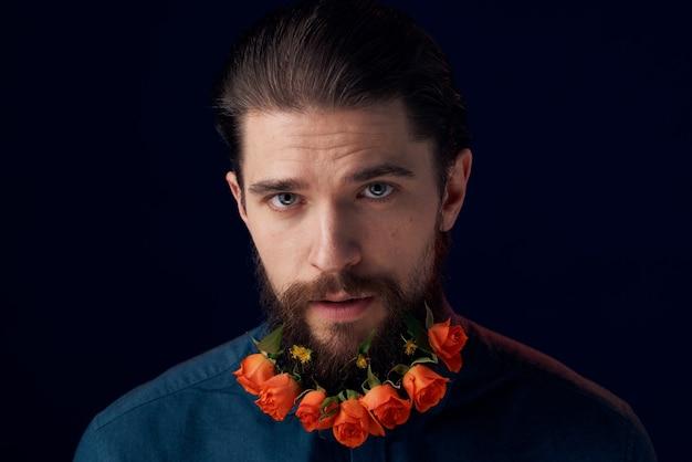 Bebaarde man bloemen in een baard close-up romantiek donkere muur.