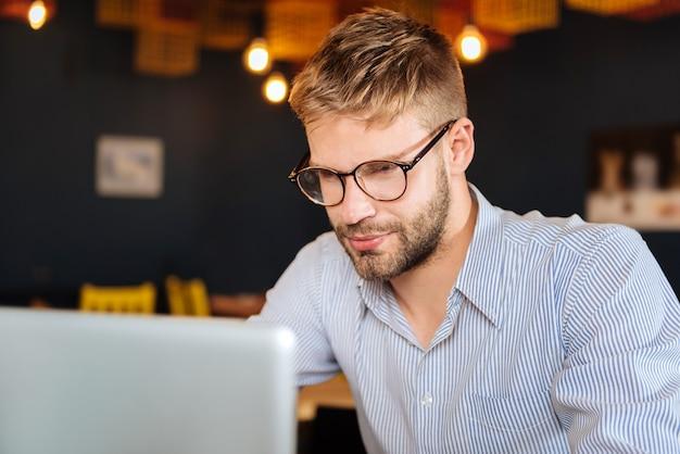 Bebaarde man. blondharige bebaarde man met stijlvolle licht shirt met bril op zoek naar zijn laptop