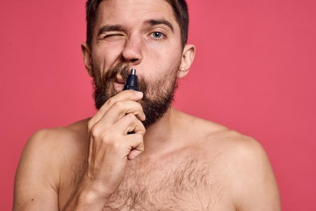 Bebaarde man blote schouders verwijdert haren uit neus lichaamsverzorging roze ruimte