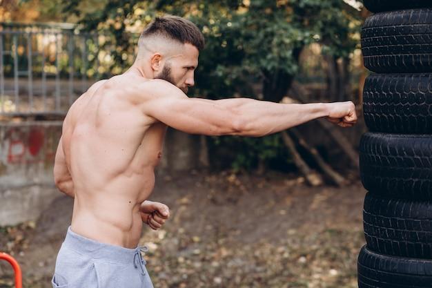 Bebaarde man boksen op straat, boksbanden, training in de tuin.