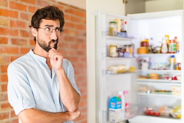 Bebaarde man denken, twijfelachtig en verward voelen, met verschillende opties, zich afvragend welke beslissing hij moet nemen