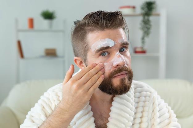 Bebaarde man die antirimpelcrème aanbrengt op zijn gezicht huidverzorging en spa voor man concept