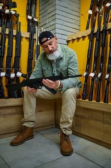Bebaarde man die automatisch geweer kiest in wapenwinkel. wapenwinkelinterieur, munitie- en munitie-assortiment, vuurwapenkeuze, schiethobby en levensstijl, zelfbescherming