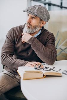 Bebaarde man die een boek leest en aan tafel zit